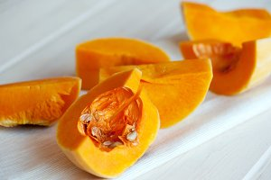 Raw orange pumpkin pieces on the background of textile and wood