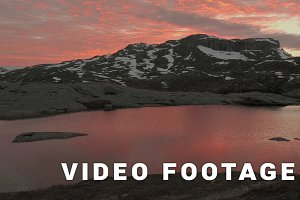 Sunset over the mountains lake, windy. Trolltunga, Norway. Smooth dolly shot
