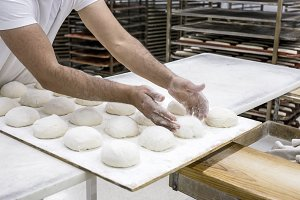 Hands hold the dough and the bread