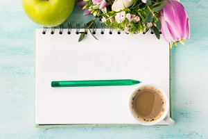 Blank notebook page with pen and cup of coffee