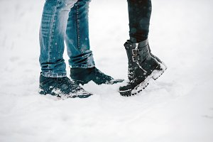 legs embracing couples standing on the snow