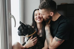happy couple and a dog at home