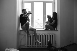 man photographs the girl at the window