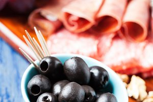 Charcuterie assortment and black olives on wooden background