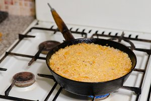 An old frying pan on the stove pilaf
