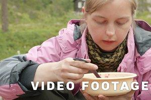 Girl eats soup outdoors