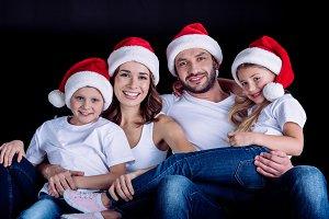 family sitting in Santa hats