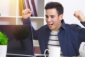 male young celebrating with enthusiasm ahead of the computer laptop