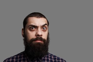 Surprised bearded man with wide open eyes and big moustache. Studio close up portrait of tanned skin hipster isolated on grey background. Serious and brutal person look to the camera. Copy space for advertising text.