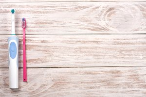 electric and manual toothbrushes on the wooden background with copy space for your text. Top view
