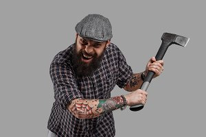 Aggressive bearded man with axe portrait isolated on neutral grey background. Shouted man run into camera. Dangerous brutal person with evil face. Natural angry emotion. Copy space for sales discounts.