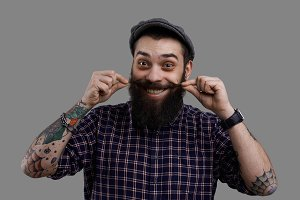 Cheerful happy long beard and big mustache man with wide smile. Joyful emotion on tense face of big kind tattooed guy in shirt. Isolated portrait on neutral grey background looking to the camera.