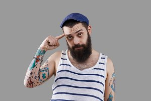 Are you crazy emotion. Tattoed funny man keep finger near head. Body language show negative opinion. Lazy person isolated on neutral grey background.