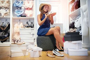 Elegant young woman trying on shoes in a store