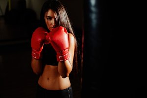 fighter girl in gym with boxing bag