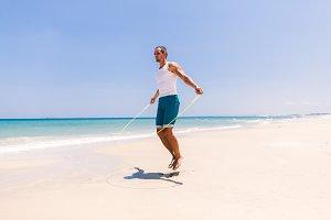 fitness man skipping on beach