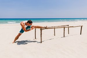 fitness man stretching on the beach