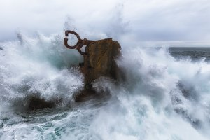 Waves splashing in El peine de los vientos, Chillida's sculpture sited in Donostia, Spain, on March 2017