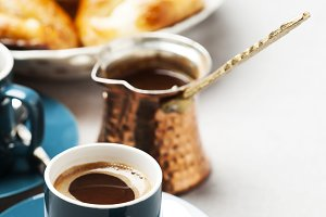 Turkish coffee in cezve and cups with pastry on background
