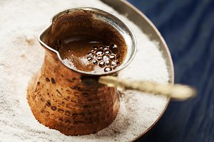 Turkish coffee made in cezve (traditional coffee pot) on sand