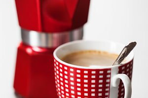 Red and white cup of coffee and percolator