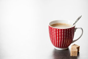 Red and white cup of coffee and brown sugar