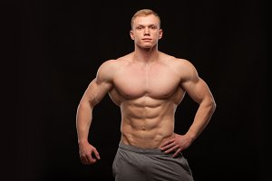 Athletic handsome man fitness-model showing six pack abs. isolated on black background with copyspace