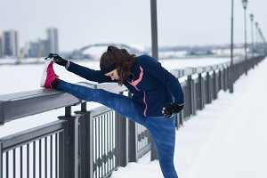 Fitness girl with pink sneakers doing stretching outside at snow winter outdoor
