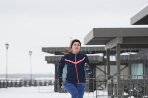 Young caucasian woman fitness model running at snow winter park - sport background