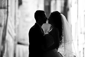 Couple kissing between old buildings