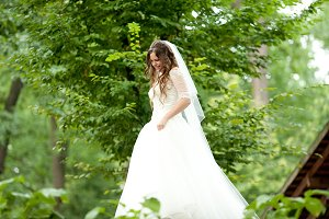 Bride walks around a green garden