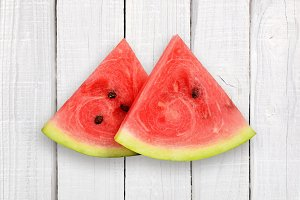 Two watermelon slices on white wood