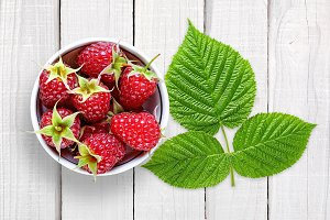 Raspberry with leaves on white wood