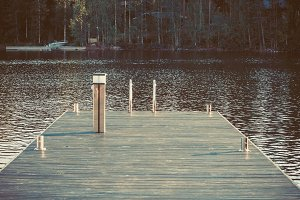 Vintage toned dock or pier on lake in summer day. forest,  Finland