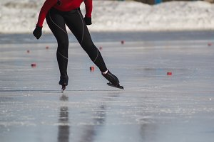 Woman's legs on skates ice rink - winter sport at sunny day