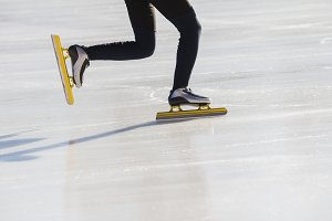 Golden skates at ice rink - winter sport concept