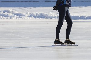 Man's legs on skates ice ring - winter sport at sunny day