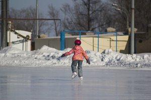 Rear view of little girl on ice-rink - children's skating sport