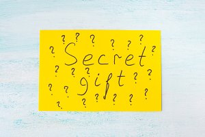 Secret gift concept yellow card on pastel flat lay