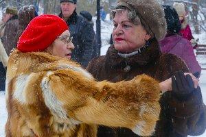 Older women in winter in the snow dance in fur coats in the park