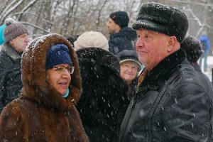 Mature man and woman in winter in a snowfall dance in the park