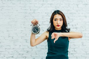 Asian business woman showing thumbs down and holding alarm clock - indicating that not pleased with time management