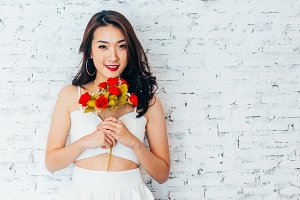 Young happy Asian woman smiling in fashionable dress and holding bouquet of roses over white wall background