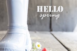 hello spring rustic concept, daisy and boots on a vintage table,
