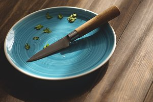 Knife and blue plate on wooden table. Horizontal shoot.