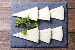 Top view of sliced cheese on slate plate. Horizontal shoot.