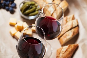 Red wine with bread and grapes on the background