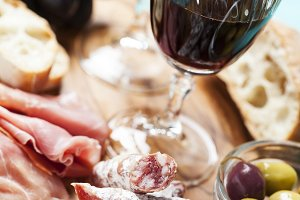 Red wine with appetizer assortment on the background