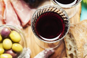 Red wine with appetizer assortment on the background, toned