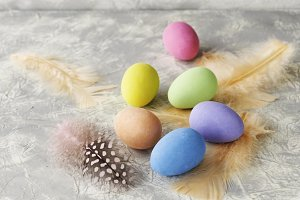 colored Easter eggs with feathers on a marble white table, selective focus